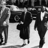 Rosa Parks being escorted to jail by two men.