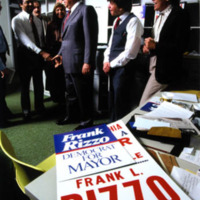 Frank Rizzo speaks with a group of people in front of his campaign poster