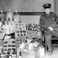 a police officer sitting in a chair next to a large pile of confiscated liquor bottles and other containers