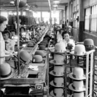 Woman in a factory sewing trimmings on hats.
