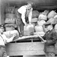 three officers standing around the opening of a truck full of burlap sacks, one of them standing in the truck and smiling at the camera, and one of them looking down at a glass bottle in his hands