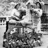 Two women decorating a carousel horse sculpture surrounded by potted flowers.