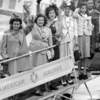A group of Puerto Rican woman waving from the boarding ramp of an airplane.