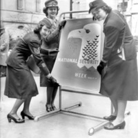 Three female officers in uniform holding a poster promoting National Security Week.