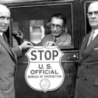 "one man inside a car, flanked by two men outside of the car, all three of them looking into the camera and holding up a sign that reads ""STOP, U. S. Official Bureau of Prohibition"""