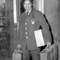Female railroad station porter carrying luggage.
