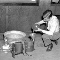 a man kneeling on the floor, pouring liquid through a funnel into a hollowed-out vest