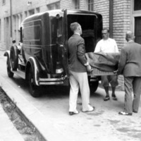 three men loading a body wrapped in a black sheet into the back of a hearse