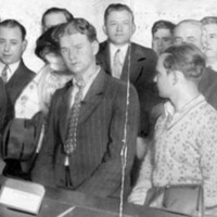 men and women lined up in a court room, some of them hiding their faces from the camera with their hands