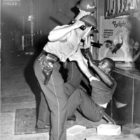 Two police officers subdue a man during a riot.