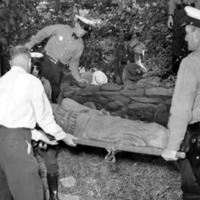 four police officers negotiating a gurney with a body wrapped in a burlap sack into the back of an ambulance in the woods
