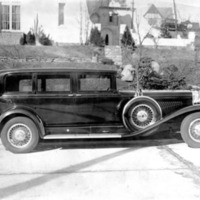 an old-fashioned black Dusenberg car with large wheels
