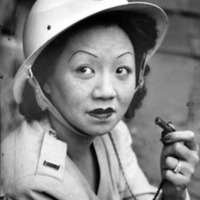 Female civil defense worker in uniform holding a whistle.