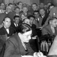 a crowd of men sitting in a court room, listening attentively while a stenographer takes notes in the foreground