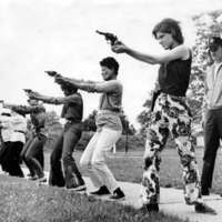A row of female police trainees at shooting practice.  Behind them, a male instructor supervises their training.