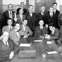 a large group of men and one woman sitting and standing around a long table, posing for a group photo
