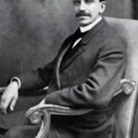 a young Russell Conwell, dressed in a suit, sitting in an upholstered chair, with his signature appearing across the bottom of the photograph