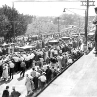 crowds of people, some of whom are standing on a roof to get a better look, crowding around the sides of a street as a funeral procession of cars drives by