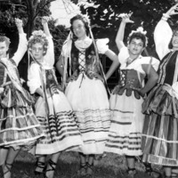 Five young women dancers in traditional Polish folk costumes.