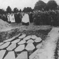 Mourners and clergy stand before an open mass grave containing the coffins of victims of the Lusitania sinking during a burial ceremony at Queenstown, Ireland, on May 10th, 1915.