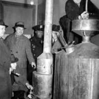 five police detectives gathered around two stills, one of them squatting on top of the still, trying to dismantle it by dislodging the pipe running from the top