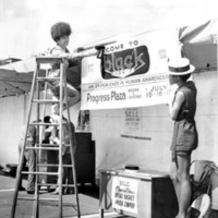 Two women hanging up signs for the 1971 Black Expo.