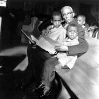 An elderly man sitting in a church pew with two young boys.