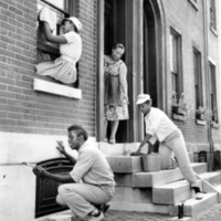 A group of 3 young people cleaning and detailing a row home while the home's occupant looks on from the door.