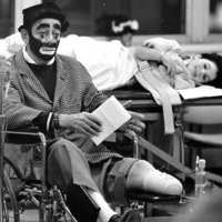 A man dressed as a clown sits in a wheelchair in front of a young boy patient