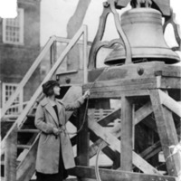 A woman pulling on a rope to ring the Woman's Justice Bell.