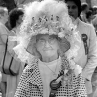 An elderly woman wearing an very elaborate bonnet and a prize ribbon on her jacket.