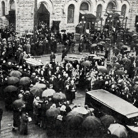 black and white image of a crowd of people, many holding large black umbrellas, in the street outside of a church, standing to the sides as a funeral procession moves through the square