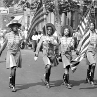 Uniformed members of the Quaker City Drum and Bugle Corps march in parade holding American flags.