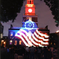 A digital projection of the Betsy Ross flag onto Independence Hall