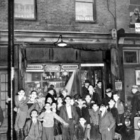 large crowd of children posing for a group photo outside of a grocery store